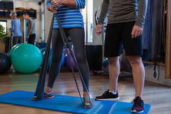 Male physiotherapist helping patient in performing exercise with resistance band Royalty Free Stock Photo