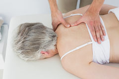 Male physiotherapist massaging a senior womans back Royalty Free Stock Photo