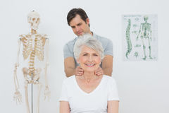 Male physiotherapist massaging a senior womans neck Royalty Free Stock Image