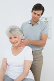 Male physiotherapist massaging a senior womans neck Royalty Free Stock Photo