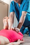 A male physiotherapist is stretching the knee joints to a young girl patient. Manual Wellness Therapy.  royalty free stock photography
