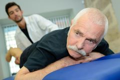 Male physiotherapist takes care senior man in office Royalty Free Stock Images