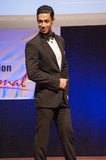 Male physique model shows his best in suit on stage Stock Photo