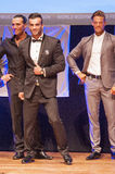 Male physique model shows his best in suit on stage Stock Photos