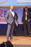 Male physique model shows his best in suit on stage Stock Images