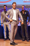 Male physique model shows his best in suit on stage Royalty Free Stock Image