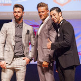 Male physique models show their best in suit on stage Stock Photo