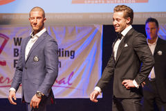 Male physique models show their best in suit on stage Royalty Free Stock Photography