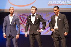 Male physique models show their best in suit on stage Stock Photos