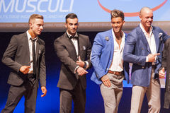 Male physique models show their best in suit on stage Stock Photography