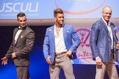 Male physique models show their best in suit on stage Stock Image