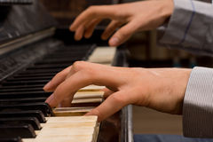 Male pianist playing music on an ivory keyboard Royalty Free Stock Image