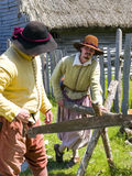 Male Pilgrims. PLYMOUTH, MA - July 24, 2009 - Male pilgrims saw wood at Plimoth Plantation.  The plantation features the recreation of an English village in 1627 Royalty Free Stock Photography