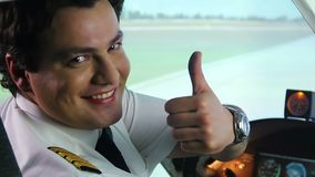 Male pilot smiling in cockpit, showing thumbs up hand sign, air transportation. Stock footage stock video