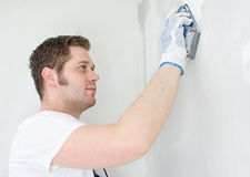 Male plasterer. In uniform polishing the wall Stock Photos