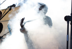 Male play on electric guitar. Rock band, music, artistic. Smoking Stock Image