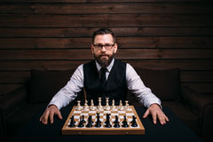 Male player against chess board with pieces set Stock Photo