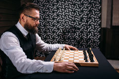Male player against chess board with pieces set Royalty Free Stock Images