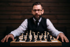 Male player against chess board with pieces set Royalty Free Stock Photo