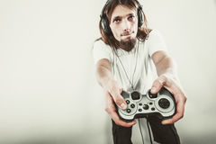 Male player focus on play games. Lifestyle of young people. Student man spending time on playing games videogames console playstation. Long haired guy focus on Royalty Free Stock Photography