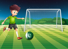 A male player kicking ball with flag of Pakistan Royalty Free Stock Photo