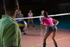 Male player playing volleyball with teammates. At court Royalty Free Stock Images