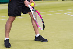 Male player`s hand with tennis ball getting ready to serve on a Stock Image