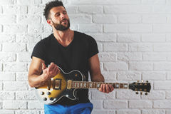 Male playing the guitar. Portrait of attractive caucasian male playing the guitar on white brick wall background. Rehearsal concept Royalty Free Stock Photos