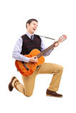 Male playing a guitar and singing. Full length portrait of a male playing a guitar and singing  against white background Stock Photos