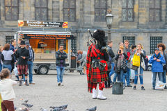 Male playing Scottish traditional pipes in Amsterdam royalty free stock photo
