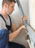 Male plumber. Male plumber assembling water pipes Royalty Free Stock Images