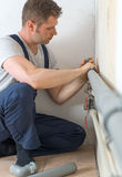 Male plumber. Male plumber assembling water pipes Royalty Free Stock Image