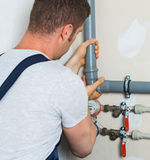 Male plumber. Male plumber assembling water pipes Stock Images