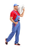Male plumber carrying a toilet. Full length portrait of a cheerful male plumber carrying a toilet and a plunge isolated on white background Stock Images