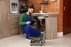 Male plumber with clipboard near kitchen sink. Repair service stock photo