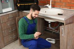 Male plumber with clipboard near kitchen sink. Repair service stock photos