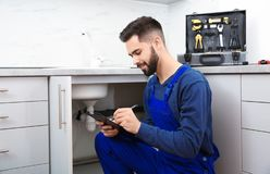 Male plumber with clipboard near kitchen sink. Repair service royalty free stock photo