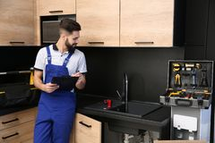 Male plumber with clipboard near kitchen sink. Repair service stock image