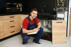 Male plumber with clipboard near kitchen sink. Repair service royalty free stock photography