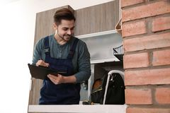 Male plumber with clipboard near kitchen sink. Repair service stock images