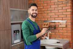 Male plumber with clipboard near kitchen sink. Repair service stock photography