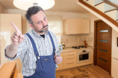 Male plumber doing refusal gesture. Male plumber with spanner doing refusal or no gesture in the kitchen with advertising area Royalty Free Stock Image
