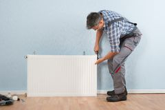 Male plumber fixing radiator Stock Photos