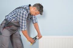 Male plumber fixing radiator Royalty Free Stock Image