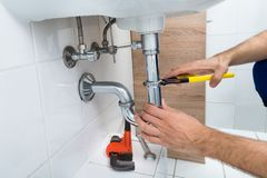 Male plumber fixing sink in bathroom Royalty Free Stock Photo