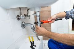 Male plumber fixing sink in bathroom. Close-up Of Male Plumber Fixing Sink In Bathroom stock photography