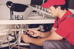 The plumber repairs the pipes. Male specialist plumber repairs. Stock Images