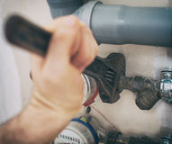 Male plumber. Male plumber fixing water meter with adjustable wrench Royalty Free Stock Photos