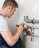 Male plumber. Male plumber fixing water meter with adjustable wrench Stock Photos