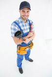 Male plumber holding plunger and wrench Stock Photo